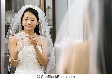 Bride looking at bouquet.