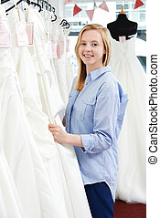 Bride Looking At Wedding Dresses In Bridal Boutique
