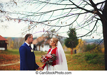Bride looks at a groom standing under an autumn tree