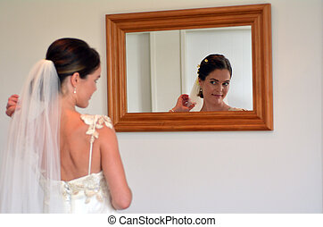 Bride looks at herself in the mirror on her Wedding Day