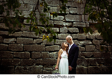Bride looks in groom's eyes while they stand behind an old stone wall