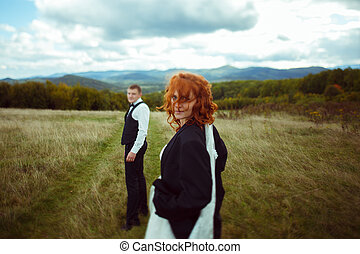 Bride looks over her shoulder being dressed in groom's jacket, standing somewhere on the field