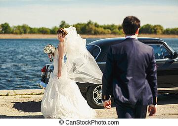 Bride looks over her shoulder on a groom standing behind an old car