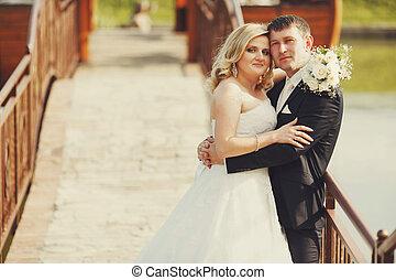 Bride looks proud being held by a groom standing on the bridge