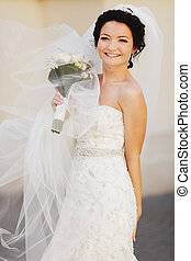 Bride looks shy smiling in the light of a warm summer day