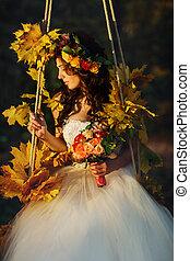 Bride looks stunning sitting on the swing full of autumn flowers