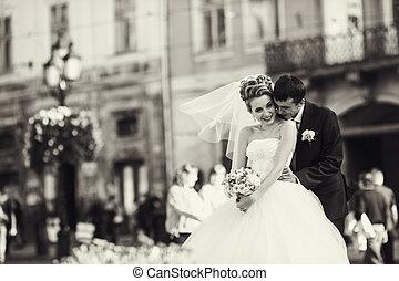 Bride looks very happy being hugged by a groom