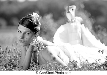 Newly married bride lying down in a field and smiling happily