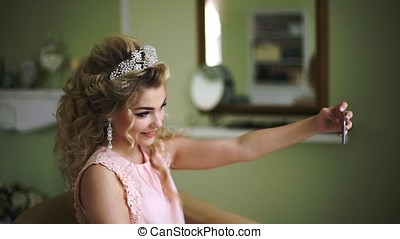 Bride makes selfie his phone. Stylish Woman Fiancee with Bridal Hairstyle, Event Makeup and Jewelry.
