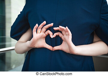 Bride making heart with fingers on grooms back
