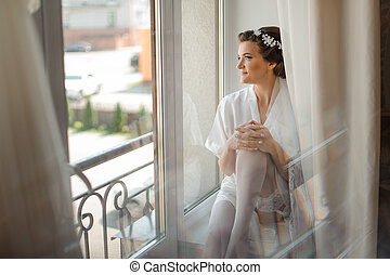 6ed1377b171 Bride morning preparation. Bride in white wedding negligee and stockings  near the window