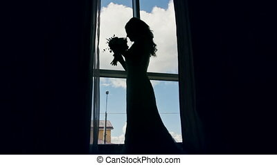 Bride near the window with her wedding bouquet, silhouette