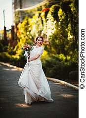 Bride on a background of trees in the park.