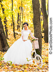 Bride on a bicycle in autumn nature