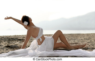 Bride on the beach - Woman in white clothes sitting on the ...