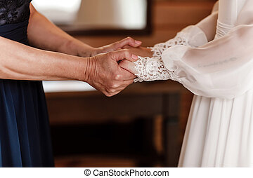 Bride on wedding day holding her mother's hands. an old woman holds her young daughter married. Concept of relationship between moms and daughters