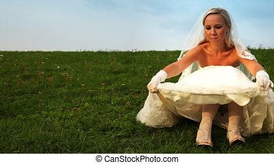 bride one sits on grass on slope of hill and corrects dress...