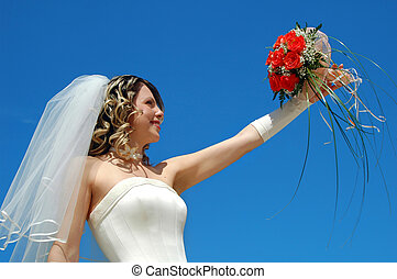 Bride - The happy bride with a bouquet of roses on a...
