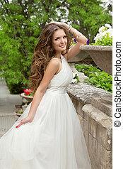 Bride Portrait Beautiful girl with long wavy hair in white weddi