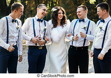 Bride posing with bridesmen in the park