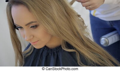 Bride prepares for wedding, making hairdo in beauty salon.