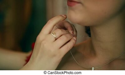 Bride preparing to wedding ceremony, her mother helps to put on jewelry