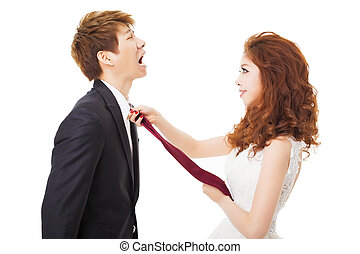 bride pulling on groom tie for control concept