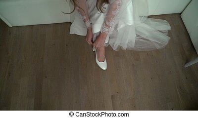 Bride puts on her wedding white shoes on high heels sitting...
