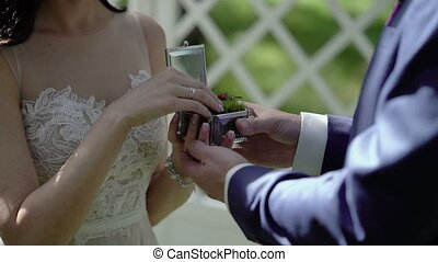 Bride puts on ring to groom hand on ceremony