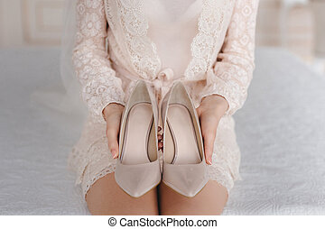 Bride puts on shoes. wedding details.