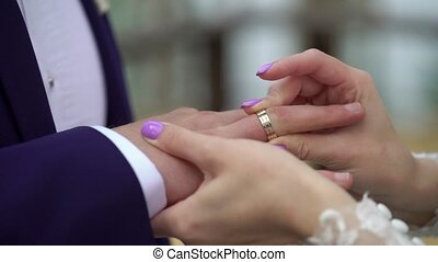 Bride putting a ring on groom's finger during wedding...