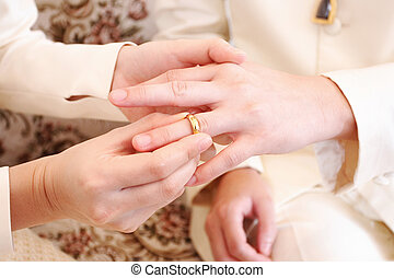 bride putting a wedding ring on groom 's finger, close up