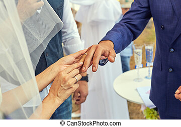 Bride putting a wedding ring on grooms finger