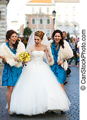 Bride screams walking with bridesmaids along the street
