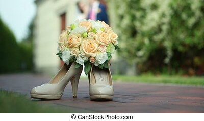 Bride shoes and flowers in focus couple in background