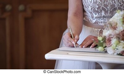 Bride signing documents at wedding ceremony