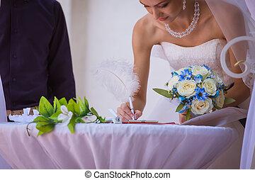 bride signing wedding certificate in park