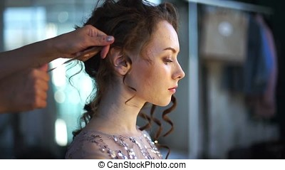 Bride sits at a beautiful studio and her hair is done.