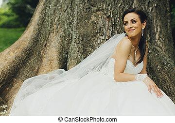 Bride sits behind an old huge tree