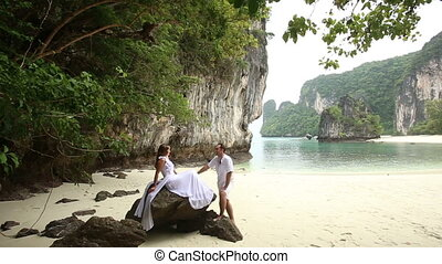 bride sits on rock and groom stands by her at sand beach
