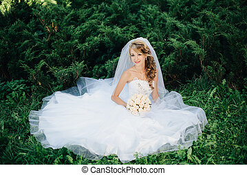 Bride sitting on green grass at park