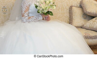 Bride sitting on sofa during photo session indoors - The...