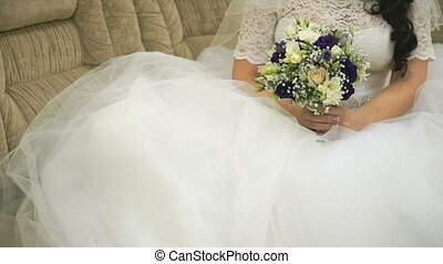 Bride sitting on sofa holds a bridal bouquet at marriage...