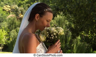 Bride smelling her bouquet in the - Bride smelling her...