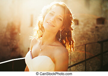 Bride smiles and shines in the light of sun