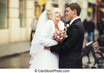 Bride smiles being hugged by a groom on the street