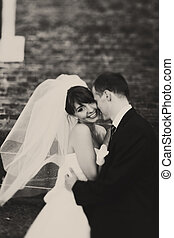 Bride smiles sparkling while being held by a groom