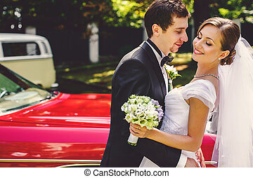Bride smiles standing in the arms of fiance behind an old red car