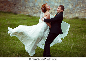 Bride smiles while a groom whirls her around