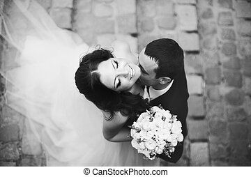 Bride smiles while groom kisses her neck tender